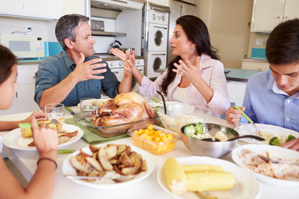 Family Having Argument Sitting Around Table Eating Meal