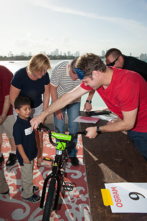 Corporate Social Responsibility (CSR) team-building event Building Bikes, Empowering Children. OSRAM team members present bicycle to deserving child. Fire Power Seminars